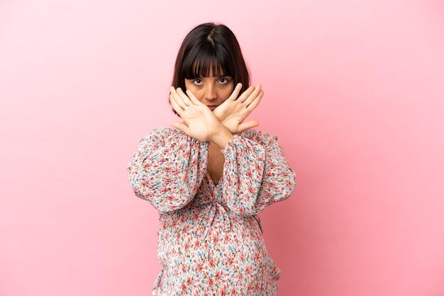 Jeune femme enceinte sur fond rose isolé faisant un geste d'arrêt avec sa main pour arrêter un acte