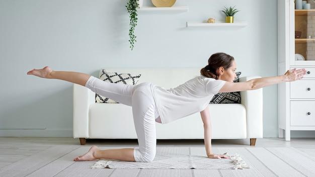 Une jeune femme enceinte gracieuse avec une queue de cheval fait du vyagrasana pratiquant la position de yoga sur un tapis de sol contre un canapé dans une pièce spacieuse à la maison vue latérale