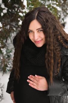 Jeune femme enceinte heureuse dans le parc enneigé