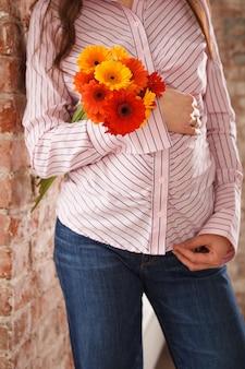 Jeune femme enceinte en jeans et chemise rose tenant un bouquet de fleurs d'été lumineuses