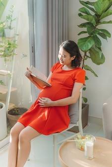 Jeune femme enceinte lit un livre