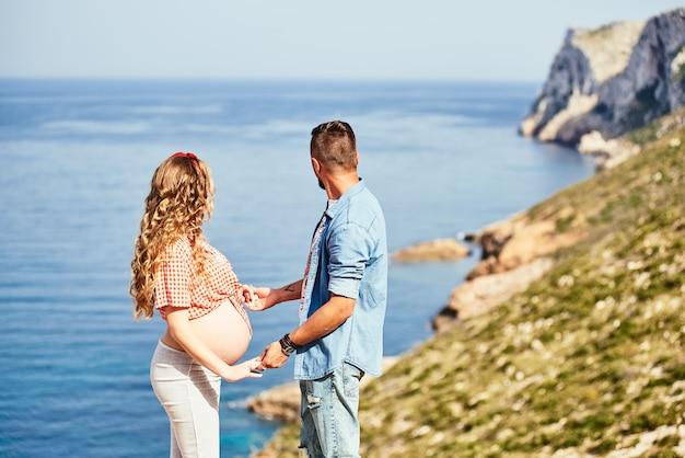 Jeune femme enceinte marchant avec son mari contre la mer