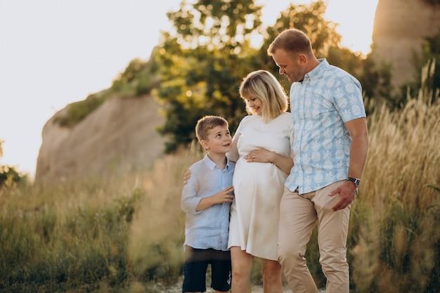 Jeune femme enceinte avec mari et fils au coucher du soleil