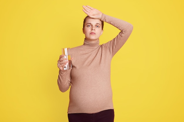 Jeune femme enceinte avec des maux de tête posant isolé sur un mur jaune et tenant un verre d'eau, gardant la paume sur le front, portant des vêtements décontractés.