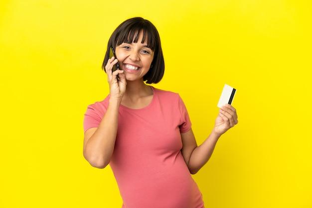 Jeune femme enceinte métisse isolée sur fond jaune gardant une conversation avec le téléphone portable et tenant une carte de crédit