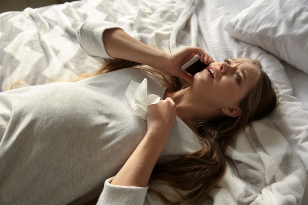 Jeune femme enceinte parlant par téléphone et pleurant à cause du changement d'humeur