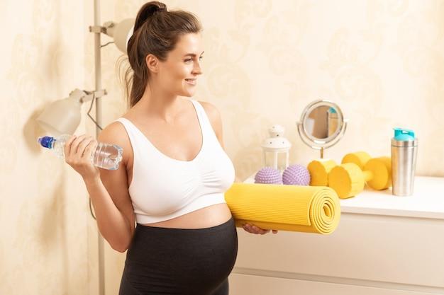 Jeune femme enceinte pendant son entraînement de remise en forme à la maison