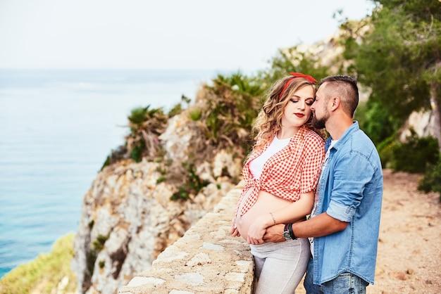 Jeune femme enceinte pose avec son mari avec vue sur la mer