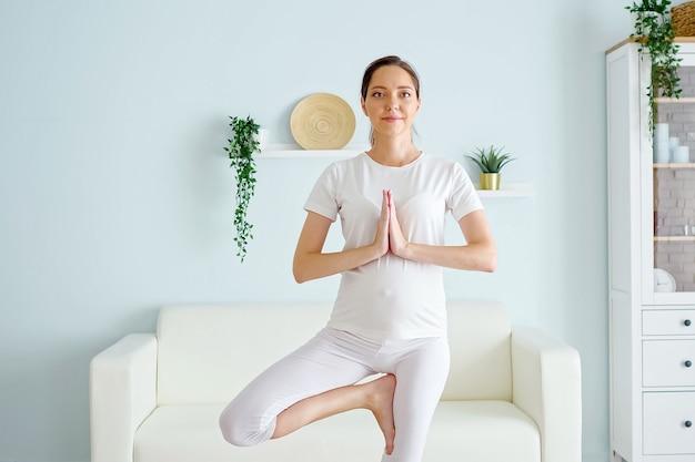 Jeune femme enceinte positive en blanc se tient en position vrksasana pratiquant le yoga contre un canapé et une armoire dans une pièce spacieuse à la maison