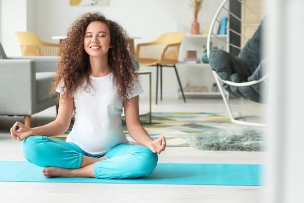 Jeune femme enceinte pratiquant le yoga à la maison