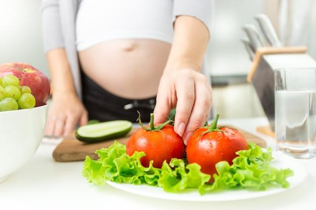 Jeune femme enceinte prenant la tomate fraîche de la plaque