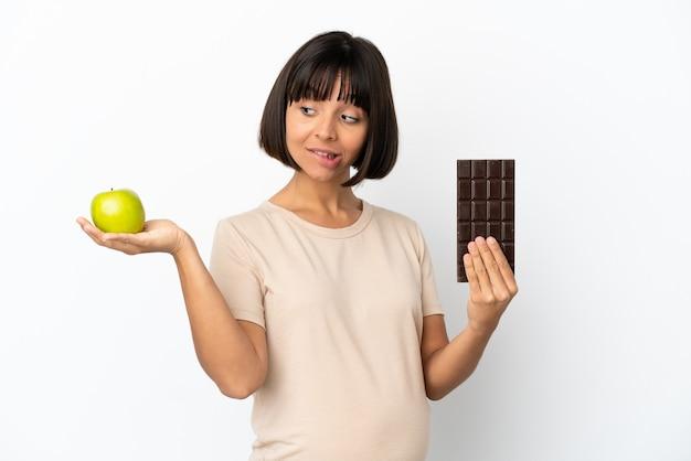 Jeune femme enceinte de race mixte isolée sur fond blanc ayant des doutes en prenant une tablette de chocolat dans une main et une pomme dans l'autre