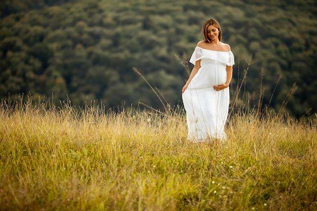 Jeune femme enceinte en robe blanche au champ d'été