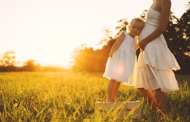 Jeune femme enceinte et sa fille en robe sur la nature à l'extérieur femme enceinte et enfant dans le pré