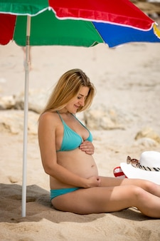 Jeune femme enceinte se détendre sur la plage et se tenant la main sur le ventre