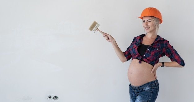 Jeune femme enceinte se dresse sur un fond blanc. vêtu de vêtements de travail. chemise à carreaux rouges et casque de chantier. indique un espace vide et des clins d'œil.