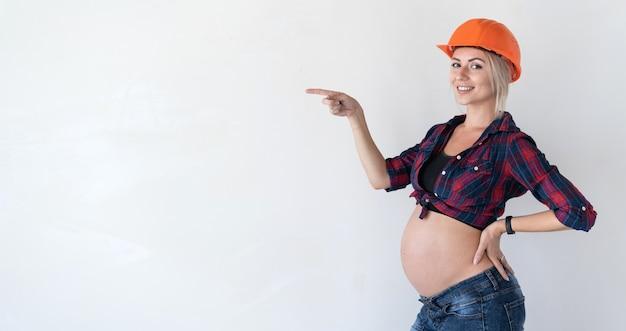 Jeune femme enceinte se dresse sur un fond blanc. vêtu de vêtements de travail. chemise à carreaux rouges et casque de chantier. pointez votre main vers un espace libre pour le texte.