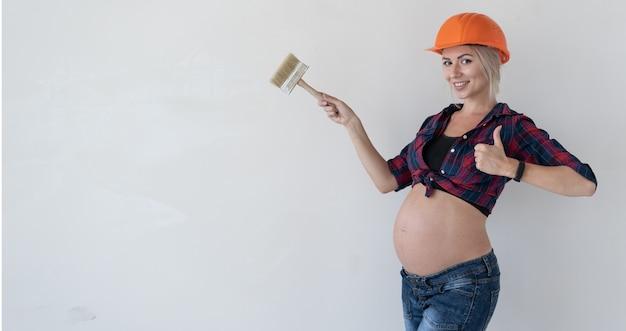 Jeune femme enceinte se dresse sur un fond blanc. vêtu de vêtements de travail. chemise à carreaux rouges et casque de chantier. tenez le pinceau dans vos mains. indique un espace vide et lève le pouce vers le haut.