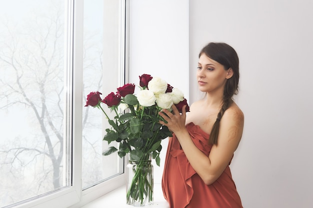 Jeune femme enceinte se tient près de la fenêtre à côté d'un bouquet de roses dans un vase