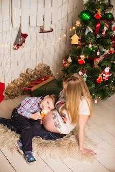 Jeune femme enceinte et son enfant célèbrent noël à la maison
