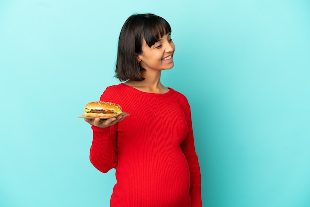 Jeune femme enceinte tenant un hamburger sur fond isolé regardant sur le côté et souriant