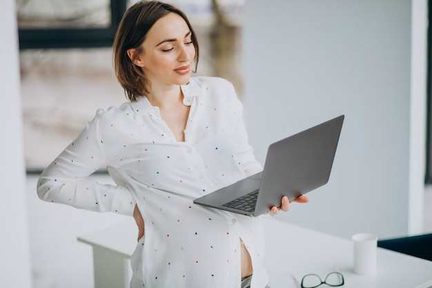 Jeune femme enceinte travaillant sur ordinateur hors du bureau