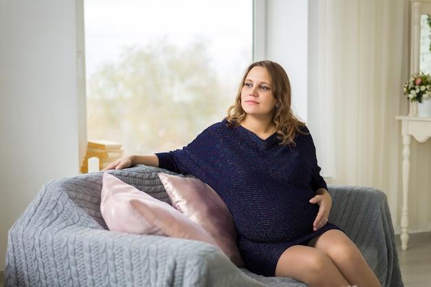 Une jeune femme enceinte vêtue d'une robe bleue est assise près d'une grande fenêtre, les mains sur le ventre. en attente d'un miracle