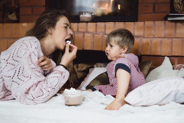 Jeune femme avec un enfant au coin du feu. mère et fils boivent du cacao au guimauve près de la cheminée.