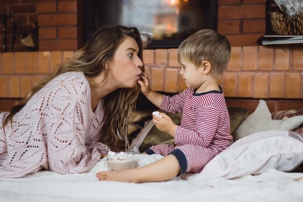 Jeune femme avec un enfant au coin du feu. mère et fils boivent du cacao avec des guimauves