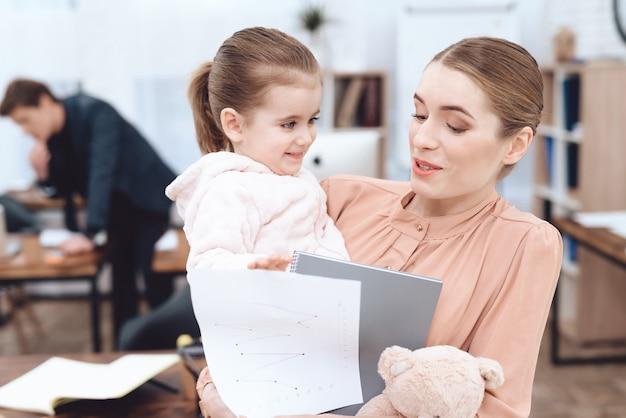 Jeune femme avec l'enfant est venue travailler.