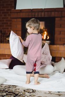 Jeune femme avec un enfant maman et son fils s'amusent autour de la cheminée.