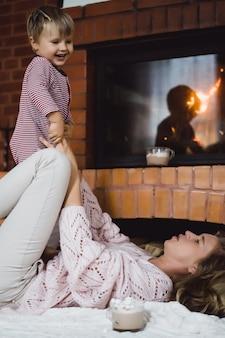 Jeune femme avec un enfant. maman et son fils s'amusent autour de la cheminée.