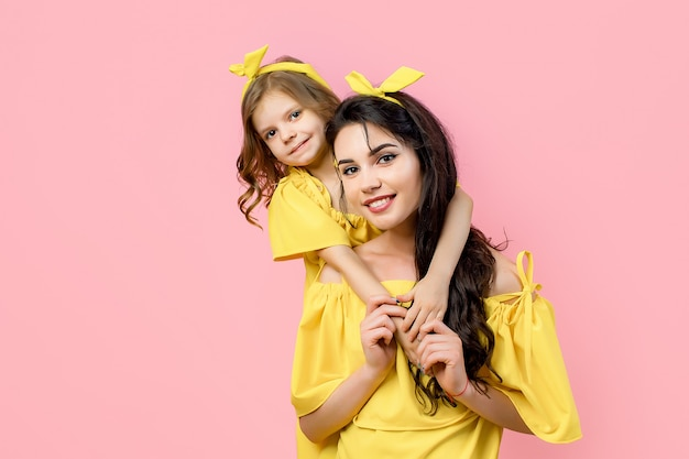 Jeune femme avec un enfant mignon qui pose en robes jaunes