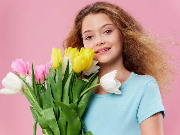 Jeune femme avec un enfant qui pose en studio avec des fleurs