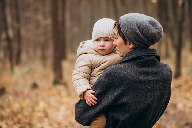 Jeune femme avec des enfants marchant dans le parc automne