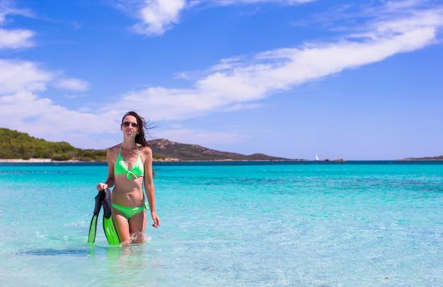 Jeune femme avec des engins de plongée en apnée sur une plage tropicale