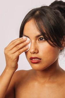 Jeune femme enlève le maquillage des yeux