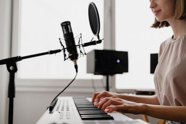 Jeune femme enregistrant une chanson à jouer du piano et chanter à la maison