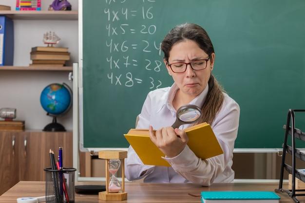 Jeune femme enseignant portant des lunettes tenant un livre en regardant les pages à travers la loupe avec une expression confiante assis au bureau de l'école en face du tableau noir dans la salle de classe