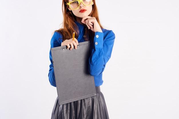 Jeune femme enseignante étudiante femme d'affaires avec dossier en mains en studio