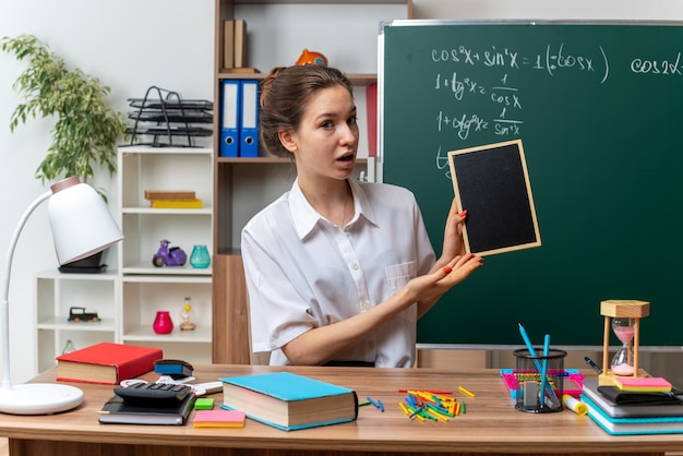 Jeune femme enseignante de mathématiques impressionnée assise au bureau avec des fournitures scolaires tenant et pointant sur un mini tableau noir regardant à l'avant en classe