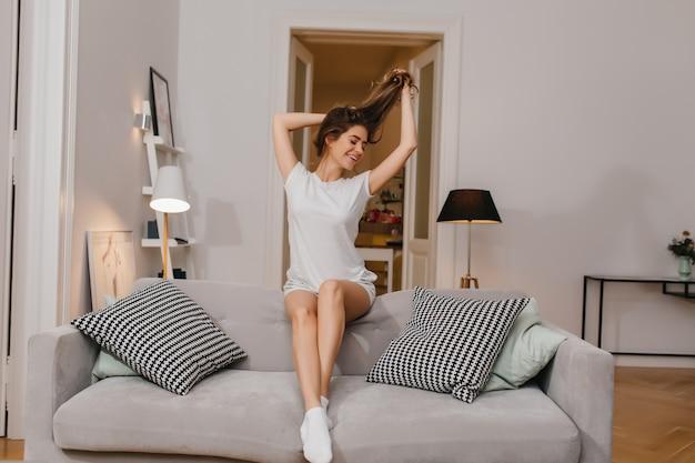 Jeune femme enthousiaste en chaussettes blanches joue avec ses longs cheveux