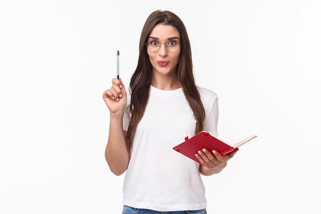 Une jeune femme enthousiaste créative a une excellente idée, l'écrivant dans son cahier pour ne pas l'oublier, levant la plume en signe eureka, souriant excité