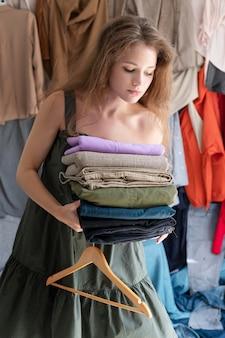Jeune femme entourée de piles de vêtements