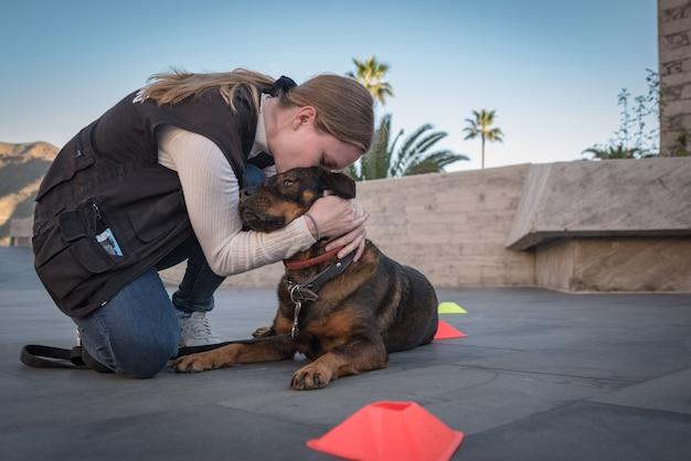 Jeune femme entraîne son chien à l'extérieur avec des jeux et des récompenses