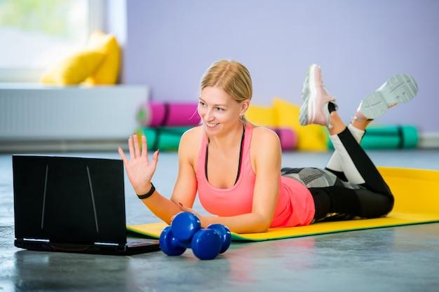 Jeune femme entraîneur effectue une séance d'entraînement en ligne devant un ordinateur portable dans la salle de sport