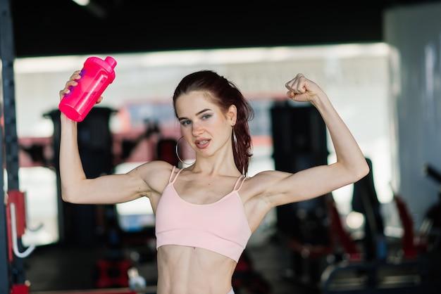 Jeune femme à l'entraîneur de gym tenant une bouteille d'eau