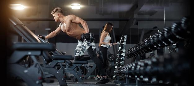 Jeune femme avec un entraîneur personnel fléchissant le dos et les muscles abdominaux sur un banc dans une salle de sport.