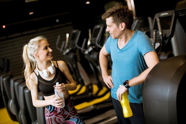 Jeune femme et entraîneur personnel se reposer dans la salle de gym après l'entraînement