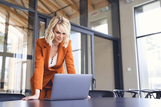 Jeune femme entrepreneur blonde ciblée, debout devant un ordinateur placé sur le bureau